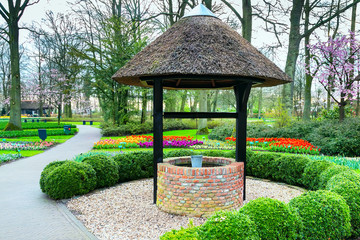 Old well in the spring flower garden and park view