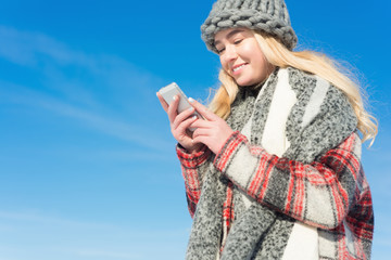 young beautiful blonde woman writes a message in the winter outd