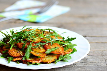 Crispy fried potatoes with arugula on a white plate and wooden table. Delicious vegetable side dish cooked with potatoes and arugula. Vegetable recipe idea. Closeup