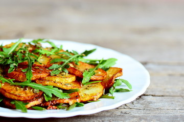 Crispy roasted potatoes with arugula on a white plate. Wooden background. Easy vegetable side dish made with potatoes and arugula. Warm salad. Vegetarian food. Closeup