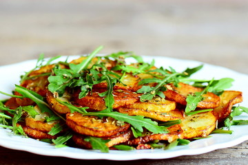 Spicy potatoes with arugula on a plate. Roasted potatoes with fresh arugula and simple dry seasoning mix. Easy and tasty vegetable side dish. Closeup