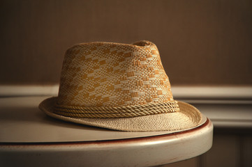 The window light is shining on the straw hat on the table