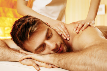 Handsome man having massage in the spa salon