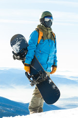 Young snowboarder getting ready to climb up the mountain