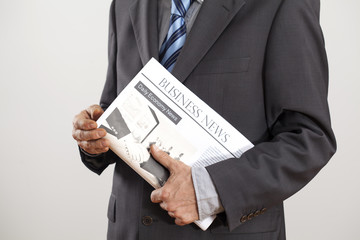 Businessman holding newspaper on gray background