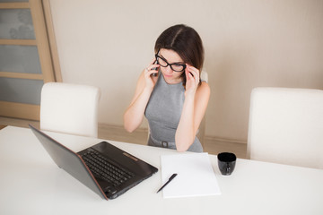 Beautiful businesswoman working on her laptop and talking on the phone while sitting at office