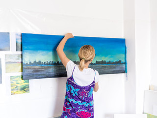 Young painter hanging up  painting in atelier