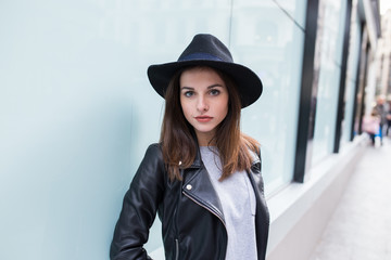 Young stylish woman against a blue wall in the street