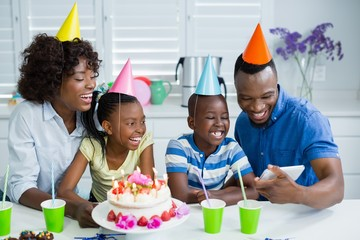 Family looking at picture while celebrating birthday party
