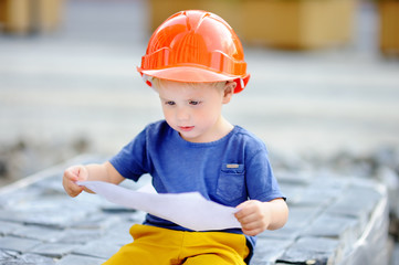 Little builder reading construction drawing