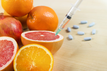 Needle and syringe injected in the fruit. Nutrition concept. Enhanced fruits. GMO. Healthy life versus unhealthy life. Fruits and pills on the table.