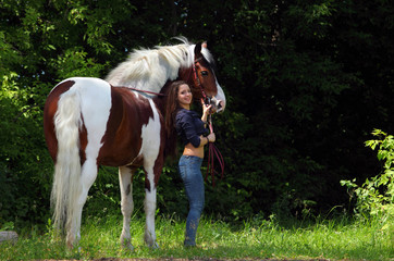 Young cowgirl with horse summer outdoor