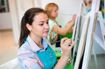 beautiful young girls draws a picture paints on art lesson