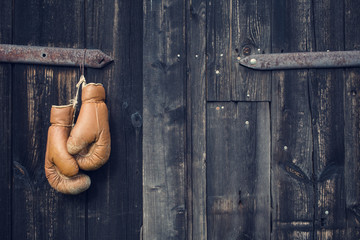 Boxing gloves hanging on old wooden door.