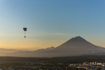 Paraglider flying over Petropavlovsk-Kamchatsky on the background of the cone of the volcano Karyaksky - Kamchatka, Russia