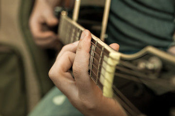 Musician's fingers on the strings of a guitar closeup