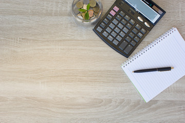 Coins, calculator and some stationery on wood table, copy space - financial background concept