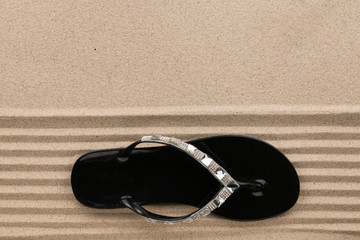 Trendy black flip flops decorated with rhinestones, standing on the beach sand.