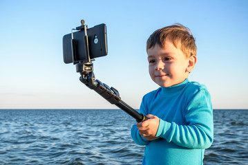 Young boy doing a selfie at the beach, kid happy and smiling loo