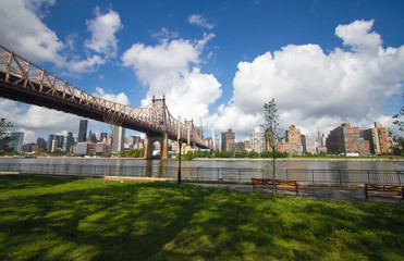 Queensboro bridge over the river and park with buildings in Manhattan, New York