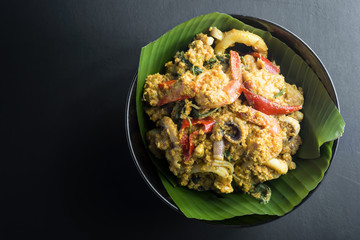 steamed fish with curry paste on black background.