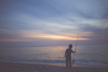 Child fishing by sea at sunset