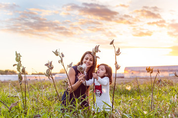 Mother and daughter blowing milk weed plants