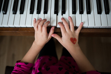 Hands of girl playing piano with love heart shape on hand