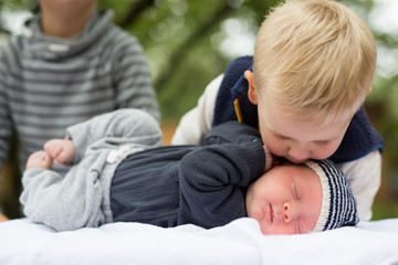 Boy kissing baby brother