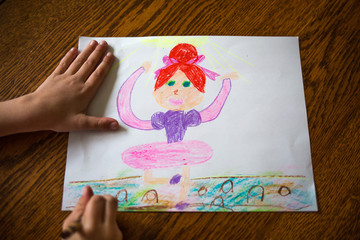 Childs hands drawing ballerina on paper