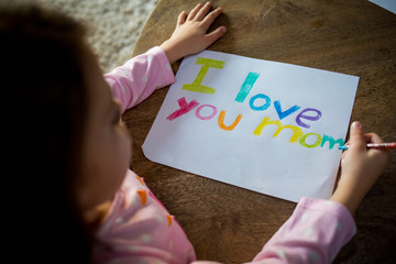 Girl writing love note to mother