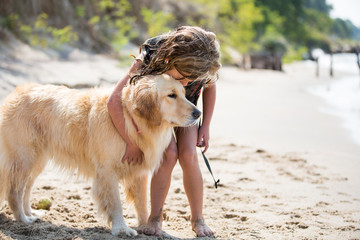 Young girl and golden retriever cuddling on beach