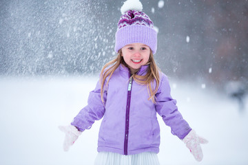 Young girl playing in snow, wearing purple hat and coat
