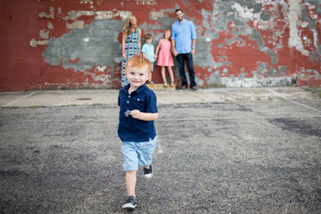 Boy running on the road while family standing in the background