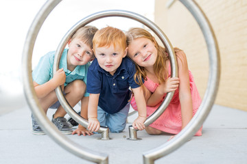 Portrait of happy children looking through steel frame