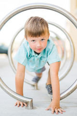 Boy crawling through circular playground frame