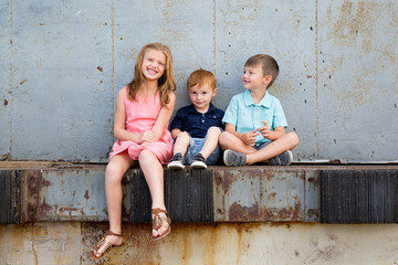 Happy children sitting on ledge together