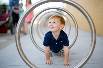 Boy crawling through circular playground frame
