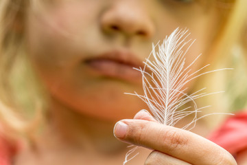 Child looking at white feather