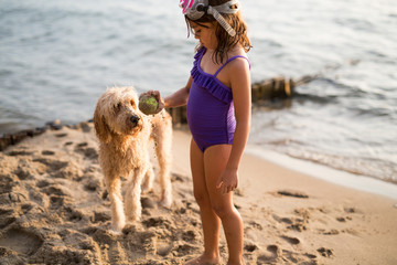 Young girl holding ball at shoreline with dog