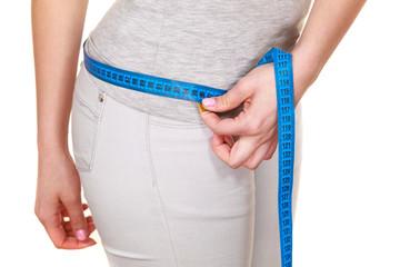 Woman measuring her hips closeup