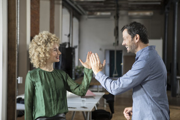 Happy man and woman high fiving in office