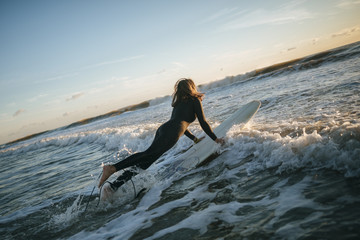 Surfer woman dressed in wetsuit entering the sea with surfboard