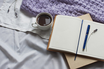 Notebook and cup of coffee with a book and a blanket of lavender on white textiles in bed