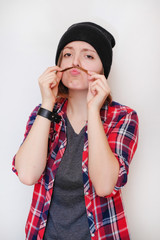 Girl hipster in a black hat, a plaid shirt, a gray t-shirt having fun and fooling around, making a fake mustache out of his hair. Closeup portrait on a isolated white background. Look into the camera.