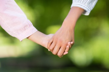Mother holding hands of her daughter in park