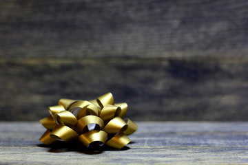 Golden bow ribbons on wooden background. Concept congratulation card background for St. Valentine`s day or birthday.