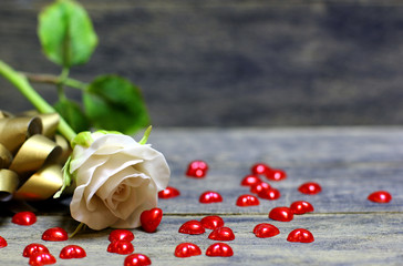 Rose flower, Small hearts scattered on the table on wooden background. Concept for banner or card background for St. Valentine`s day. Copyspace.