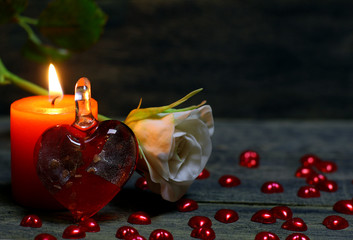 Glass heart, rose flower, Small hearts scattered on the table and burning candle on wooden background. Beautiful congratulation card background for St. Valentine`s day. Copyspace.