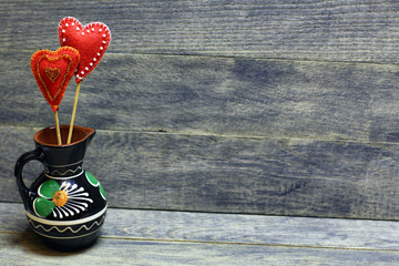 Decorative hand made hearts in small folk style vase on wooden background. Sewed from a felt and decorated with beads. Beautiful congratulation card background for St. Valentine`s day. Copyspace.